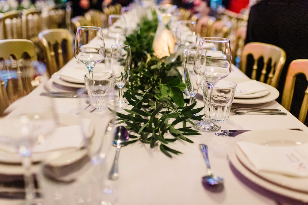 long wedding table dressed with greenery