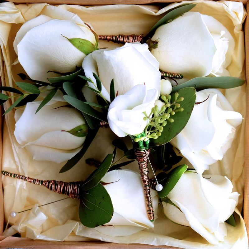 white rose buttonholes in a box