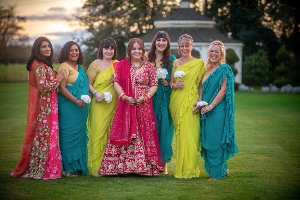 Wedding Group shot at Thornton Hall Hotel Bride in red lengha with bridesmaids in green and blue