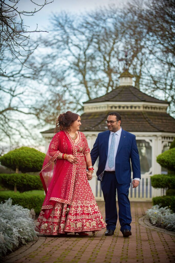 Bride in red lengha and groom in blue suit infront of pegoda at Thornton Hall Hotel Wedding